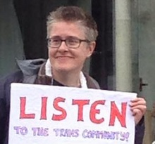 Image: Sam Hope holding a placard that reads : Listen to the trans community