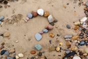 [image: a pebbled beach with some pebbles arranged to form a question mark]