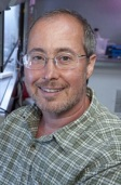 Ben Barres, a trans man and scientist, head shot, wearing checked shirt