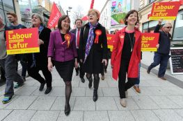 [Image: Eddie Izzard on the Labour campaign trail with two others. Izzard is wearing make-up and a skirt suit]