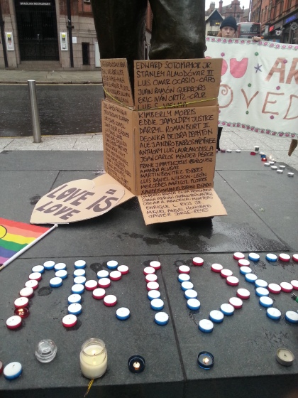A Statue plinth with the word pride written in candles. A list of the names of the Orlando victims is tied to the bottom of the statue.